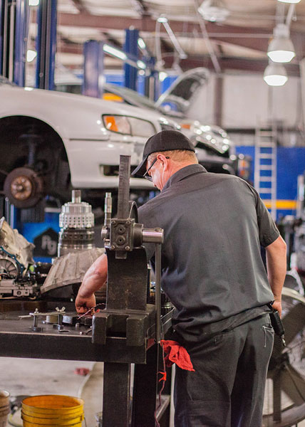 Aarrow technician handling transmission parts